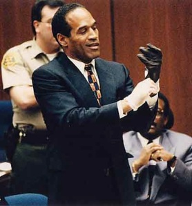 Former USC football player O.J. Simpson, putting on gloves to protect him from the bitter cold.